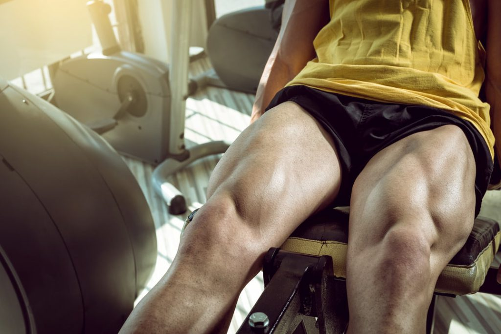 Image of a man doing leg extensions in a gym