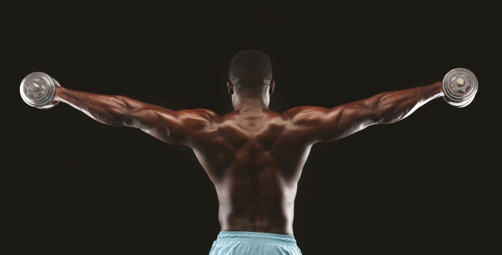 Image of an african bodybuilder raising hands pumping up dumbbells